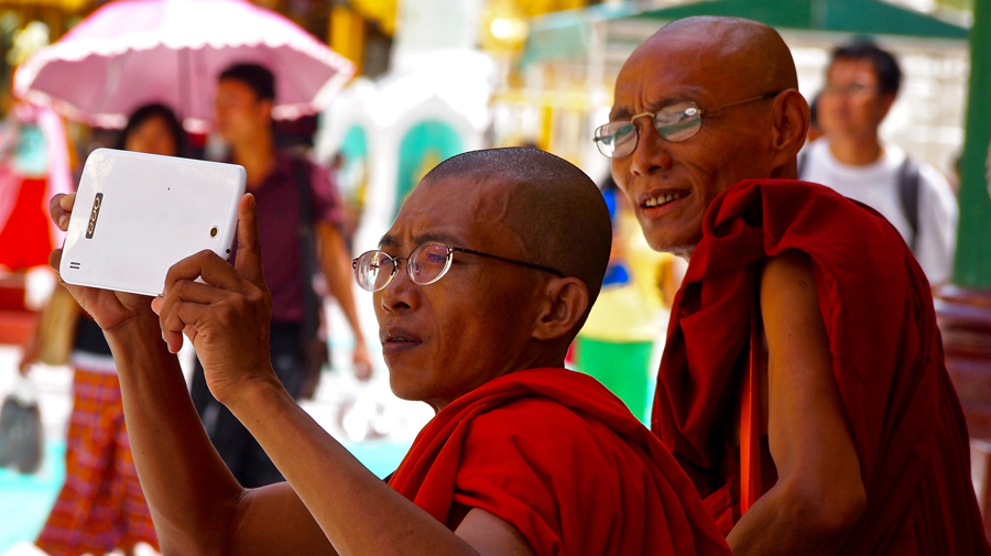 Monk using his phone at the Shwedagon Pagoda in Yangon, Myanmar.