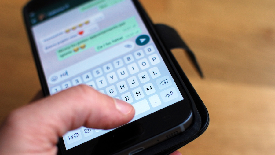Photo of someone holding a phone replying to a Whatsapp message