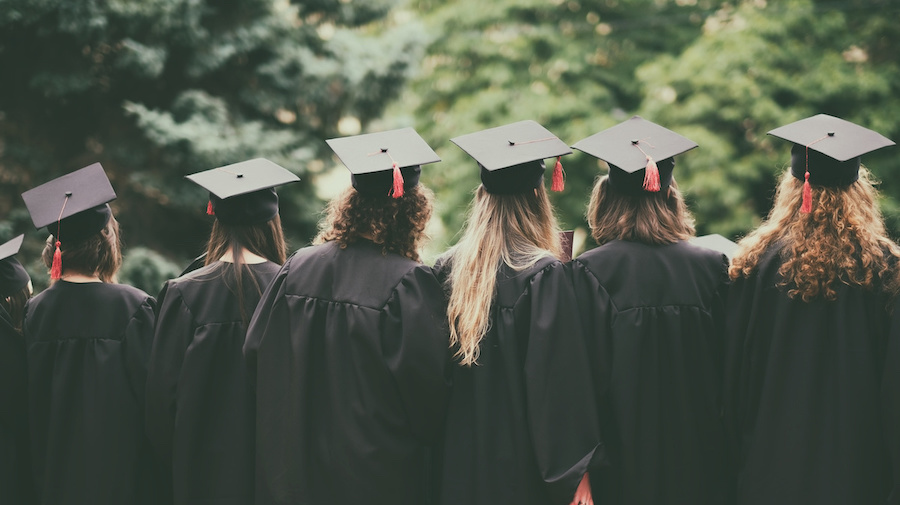 A photo of group of graduated students back view standing between trees
