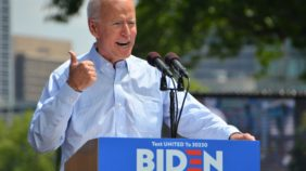 Joe Biden raises his hand in a thumbs up while giving a campaign speech at a lectern on a sunny day