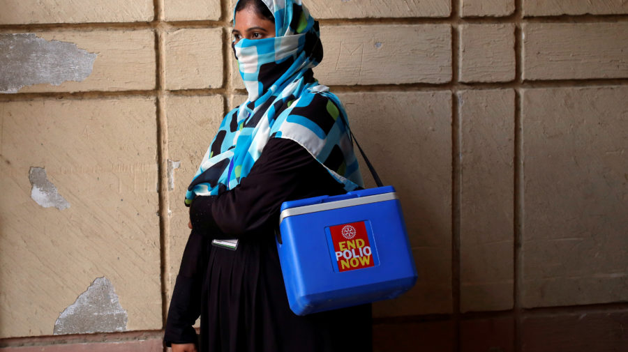 Vaccinator with kit box waits for her colleagues to do anti-polio campaign in a low-income neighbourhood in Karachi