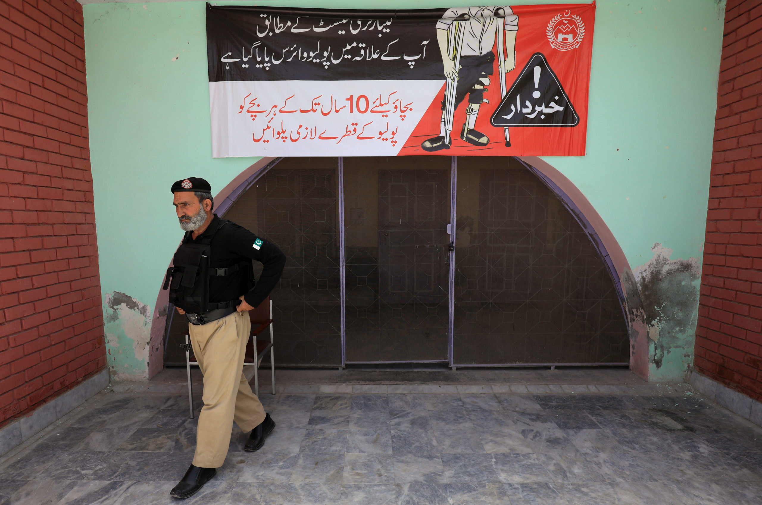 Police officer walks outside a Polio Vaccination centre in Peshawar